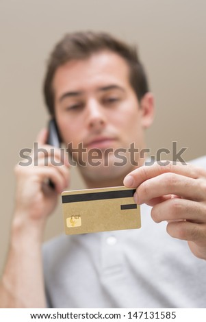 Man paying with credit card on phone - stock photo