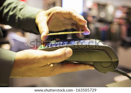 Man paying with NFC technology on credit card, in clothing store - stock photo
