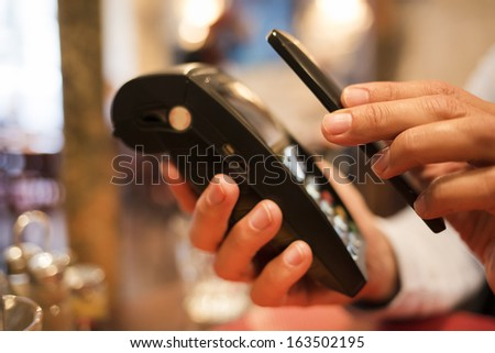 Man paying with NFC technology on mobile phone, in restaurant, bar, cafe - stock photo