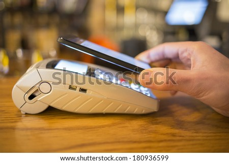 Man paying with NFC technology on mobile phone, restaurant, shop - stock photo