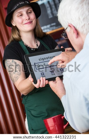 Man pays cafe bill and tip by signing with finger for credit card on a tablet - stock photo