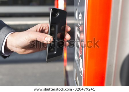 Man pays his transport ticket with his mobile phone on platform station. NFC. Contactless  - stock photo