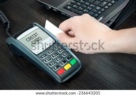 Man pays with credit card. Swiping plastic card through terminal