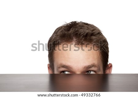 man peaking from under a desk - stock photo