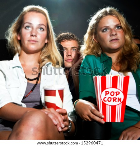 Man peeking between the two seats in front of him to get a better view of the movie on show - stock photo