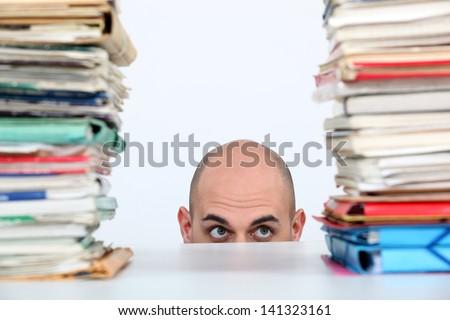 Man peeking through stacks of folders - stock photo