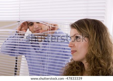 man peeking woman in the window - stock photo