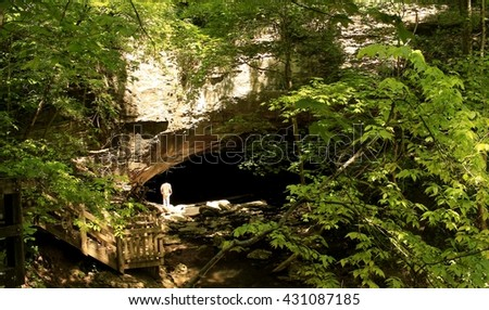 Man peering into a large cave; parks in the Midwest - stock photo