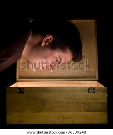Man peers into a glowing box
