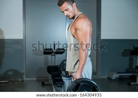 Man Performing Heavy Dead lift In A Gym - stock photo