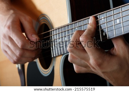 Man performing song on western acoustic guitar - stock photo
