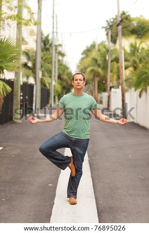 Man performing yoga in the middle of the street - stock photo