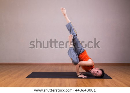 Man performs advanced yoga pose in studio