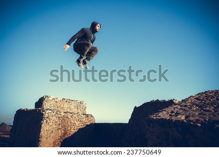 man performs freerunning jump on stones - stock photo