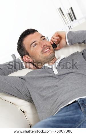 man phoning on sofa - stock photo