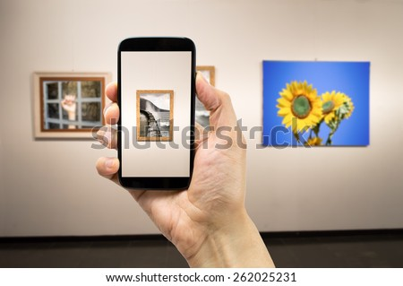 man photograph a painting at an exhibition of the museum.Background photos are my property - stock photo