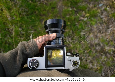 man photographer is making landscape photography with old film camera in spring or summer, tourism and hiking concept. - stock photo