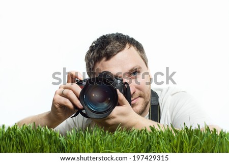 Man photographer on the green grass isolated - stock photo