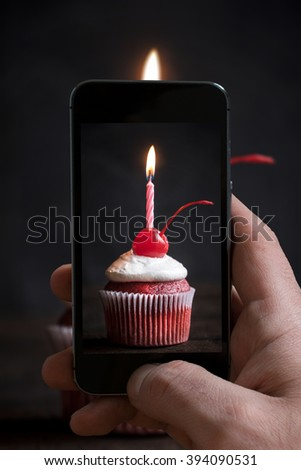 Man photographing birthday cupcake with candle on wooden background,selective focus  - stock photo