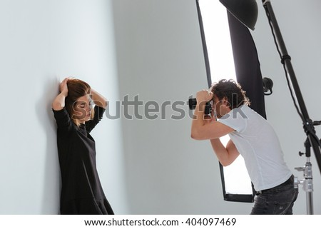Man photographing female model in professional studio with equipment - stock photo