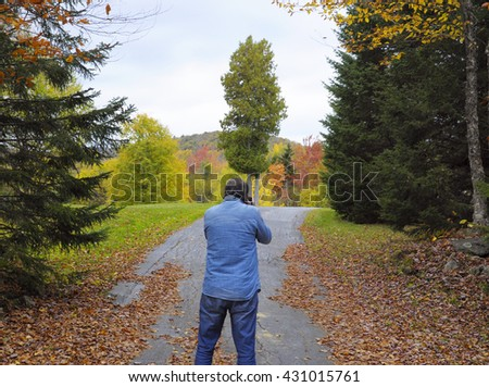 Man photographing foliage in Vermont, USA - stock photo