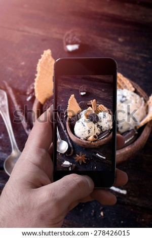 Man photographing ice cream in wooden bowl with his cellphone camera,selective focus  - stock photo