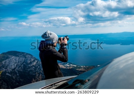 Man photographing lanscapes standing near his car on the top of mountain - stock photo