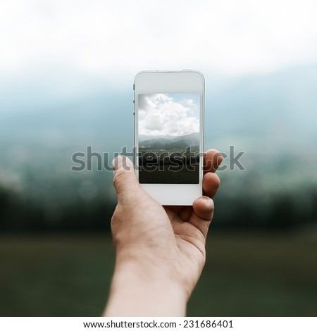 Man photographing scenery on the phone - stock photo
