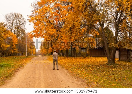 Man photographing street view of village with country road, trees and wooden house at golden autumn in Belarus on cloudy weather