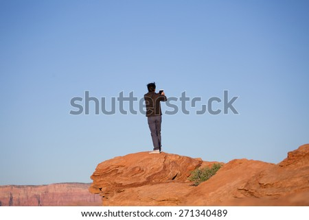 Man photographing Sunset at the canyon and the Colorado river at Horseshoe Bend, in Page, Northern Arizona, AZ, America's top travel destination, mobile or tablet photography - stock photo
