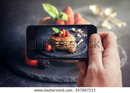 Man photographing wit his phone buckwheat pancakes with fruit  - stock photo