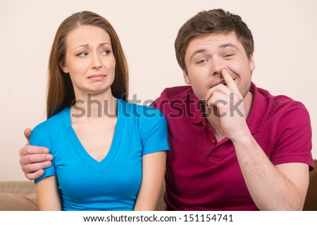 Man picking nose. Young man picking nose while sitting close to his girlfriend - stock photo