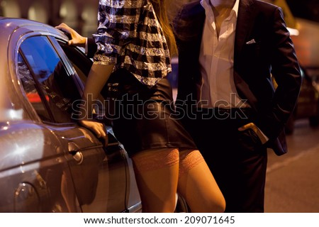 Man picking up a prostitute on the street - stock photo