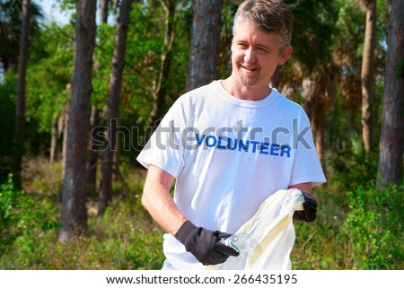 Man picking up litter during a volunteer environmental cleanup event.