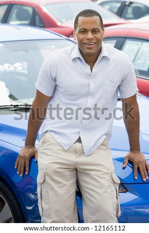 Man picking up new car from lot - stock photo