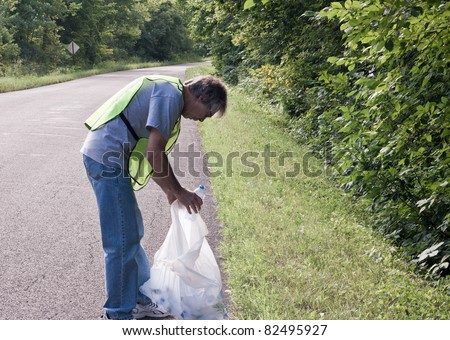 man picking up trash along a rural road - stock photo