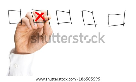 Man placing a red cross in a set of hand-drawn check boxes on a virtual interface over a white background with copyspace, close up view of his hand. - stock photo