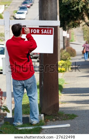 "Man placing ""for sale"" sign - stock photo"