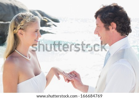 Man placing ring on pretty blonde brides finger at the beach