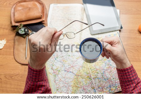 Man planning a travel destination, focus on hand with tea cup - stock photo