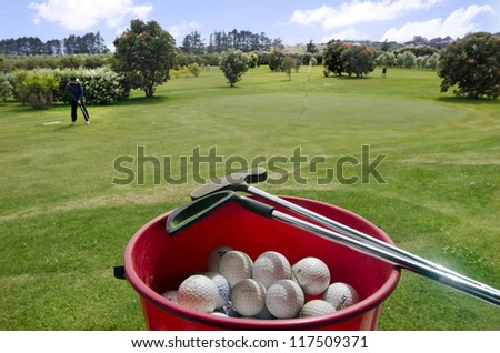Man play golf in a golf club with a red bucket full of balls in the foreground. Concept photo of golf , game, competition, training ,challenge, practice, teaching and golfing  - stock photo