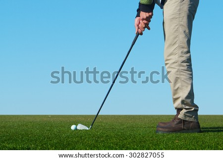 Man playing a game of golf outside - stock photo
