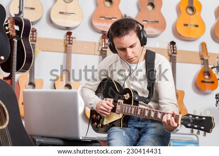 Man playing a guitar and recording her music in computer - stock photo