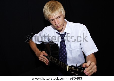 man playing a guitar isolated on black background - stock photo