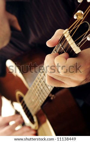 Man playing a musical instrument accoustic guitar - stock photo