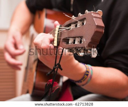 Man playing a musical instrument acoustic guitar