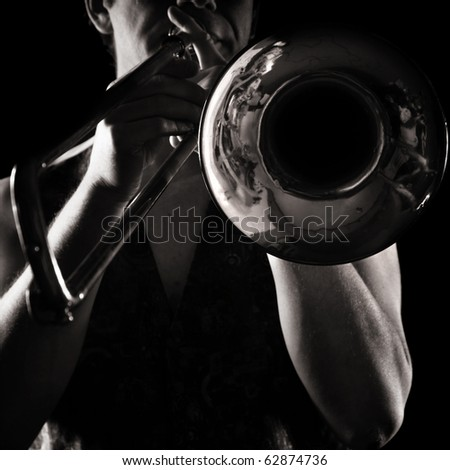 man playing a trombone; strong contrasting side-light; monochrome version; - stock photo