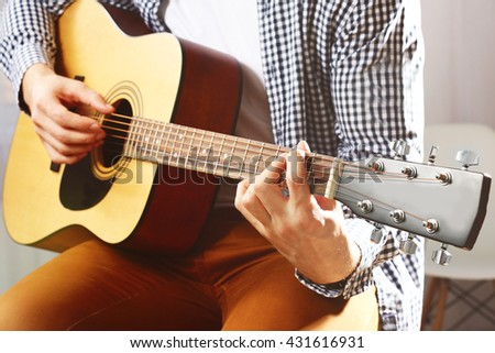 Man playing acoustic guitar - stock photo