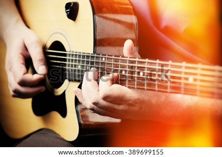 Man playing acoustic guitar at home, hand close-up.