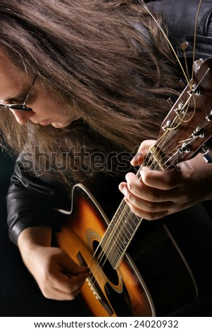 Man playing acoustic guitar at rock concert - stock photo